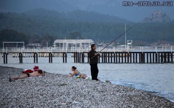 Какой-то турецкий рыбак среди загорающих.