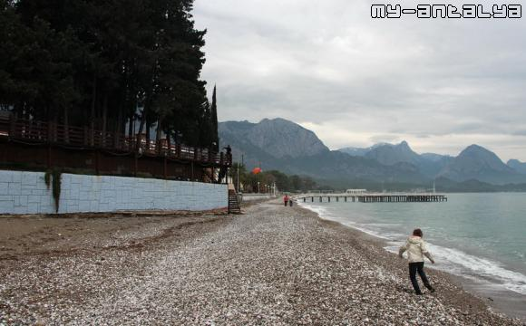 По пляжу прогуливаются одинокие туристы.