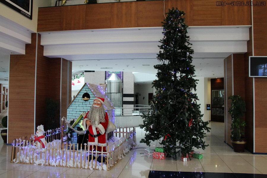 """Гостей всречают пластмассовый Дед Мороз и искусственная ёлка с """"подарками""""."""